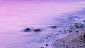 Romantische Atmosphäre am ruhigen Morgen in Meer Große Flusssteine, die heraus vom glatten gewellten Meer haften stockfotografie