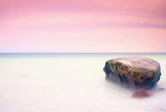 Romantische Atmosphäre am ruhigen Morgen in Meer Große Flusssteine, die heraus vom glatten gewellten Meer haften Rosa Horizont stockfotografie