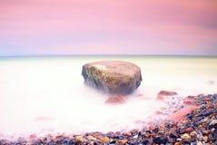 Romantische Atmosphäre am ruhigen Morgen in Meer Große Flusssteine, die heraus vom glatten gewellten Meer haften Rosa Horizont lizenzfreies stockbild