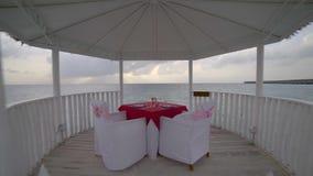 Romantische Atmosphäre am tropischen Strand, Bungalow mit Gläsern und Teller auf Tabelle im Meer gegen Wasser stock video