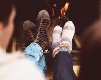 Romantische Beine eines Paares in den Socken vor Kamin am wint Lizenzfreies Stockfoto