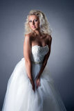 Romantische blonde Aufstellung im üppigen Hochzeitskleid Lizenzfreie Stockbilder