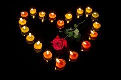 Romantische brennende geformte mit Blumenkerzen im Herzen formen mit einer hellen Rotrose an der bedeutenden Mittelliebe Stockfoto