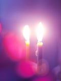 Romantische brennende Kerzen am lila Hintergrund Stockfotos