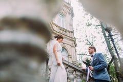 Romantische bruidegom die boeket geven aan zijn mooie bruid op de treden van de antieke Oostenrijkse bouw stock foto