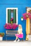 Romantische Dame, die auf Bank vor Haus sitzt lizenzfreie stockfotografie