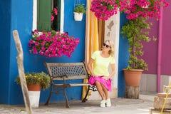 Romantische Dame, die auf Bank vor Haus sitzt Stockfotografie