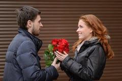 Romantische datum. Jonge mens die een bos van rode rozen voorstellen aan van hem Royalty-vrije Stock Foto's