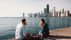 Romantische datum op de kust van het meer van Michigan in Chicago, Amerika Mooi paar die van een picknick samen genieten stock video