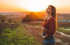 Romantische de schoonheid is zwanger Meisje die in openlucht van aard genieten die haar model van de buik Mooi herfst in aard in  royalty-vrije stock afbeeldingen
