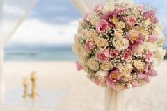 Romantische Dekoration mit Blumen einer Strandhochzeit auf dem Strand mit Meer im Hintergrund stockbild
