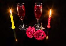 Romantische Einrichtung mit roten Rosen der brennenden Kerzen und Rotweingläsern im dunklen Hintergrund Lizenzfreies Stockbild