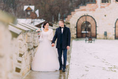 Romantische enloved Jungvermähltenpaare, die zusammen nahe alter Schlosswand schlendern Stockbilder