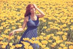 Romantische Frau auf dem Blumengebiet am sonnigen Tag Lizenzfreie Stockbilder
