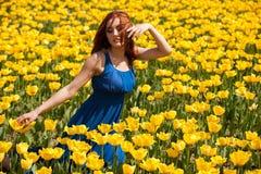 Romantische Frau auf dem Blumengebiet am sonnigen Tag Lizenzfreies Stockfoto