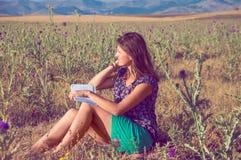 Romantische Frau, die auf dem Gebiet mit einem Buch sitzt Stockfotografie