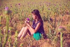Romantische Frau, die auf dem Gebiet mit einer Blume sitzt Stockfotografie