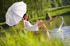 Romantische Frau, die durch den See spritzt Wasser sitzt Lizenzfreies Stockfoto