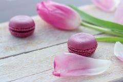 Romantische gevoelige samenstelling met roze bloemen en makaroncakes stock fotografie