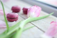 Romantische gevoelige samenstelling met roze bloemen en makaroncakes stock foto's