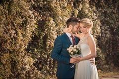 Romantische Hochzeitspaare, die an einander umfassen Stockbild