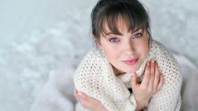 Romantische jonge Europese vrouw die warm krijgen in witte gebreide plaid verpakt stock footage