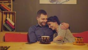 Romantische jonge paarzitting in een koffie bij een lijst het drinken koffie en het spreken dolly stock videobeelden