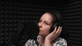 Romantische jonge vrouw in hoofdtelefoons die lied in huis vocale studio registreren Leuk meisje met lang donker haar het zingen  stock video