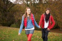 Romantische Jugendpaare, die durch Herbst gehen Stockfotos