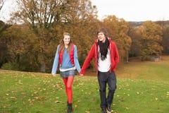 Romantische Jugendpaare, die durch Herbst gehen Lizenzfreies Stockfoto