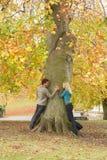 Romantische Jugendpaare durch Herbst-Park Treein Lizenzfreie Stockbilder