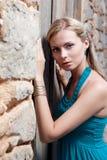 Romantische junge blonde Frau auf Steinwandrückseite lizenzfreie stockfotos