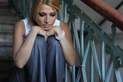 Romantische junge Frau, die auf Treppen sitzt Stockfotos