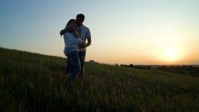Romantische junge glückliche schwangere Paare, die in der Natur bei Sonnenuntergang umarmen stockbilder