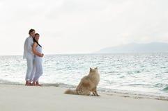Romantische junge Paare auf dem Seeufer mit Hund Stockfoto