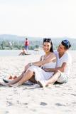 Romantische junge Paare, die an einem Strand sitzen Lizenzfreie Stockbilder