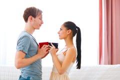Romantische junge Paare, die Geschenke austauschen Lizenzfreie Stockfotos