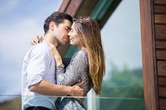 Romantische junge Paare, die im Balkon küssen Stockfotografie