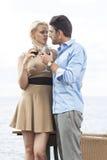Romantische junge Paare, die Rotwein Glas Restaurant am im Freien durch See halten Stockbilder