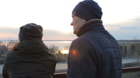 Romantische junge Paare, die Sonnenuntergang auf dem Dachbalkonstadtbild genießend sich entspannen stock video footage