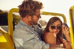 Romantische junge Paare, die Spaß auf einer Autoreise haben Lizenzfreie Stockfotografie