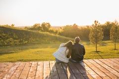 Romantische junge Paare, welche die Herbstnatur sitzt in einer nahen Umarmung, Ansicht von hinten genießen lizenzfreie stockfotos