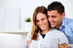 Romantische junge Paare zu Hause, die zum Laptop schauen Stockbild