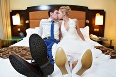 Romantische kus gelukkige bruid en bruidegom in slaapkamer Stock Afbeeldingen