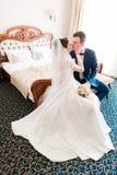 Romantische kus gelukkige bruid en bruidegom in slaapkamer op huwelijksdag Stock Foto's