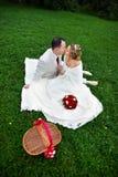 Romantische kusbruid en bruidegom op huwelijkspicknick Stock Foto's