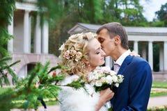 Romantische Kussbraut und -bräutigam auf Hochzeit gehen Stockfotos