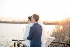 Romantische Landschaft, das Jungvermähltenpaar, das bei Sonnenuntergang nahe dem Fluss, der Bräutigam aufwirft, hält die Hand ein Lizenzfreie Stockfotos