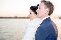 Romantische Landschaft, das Jungvermähltenpaar, das bei Sonnenuntergang nahe dem Fluss, der Bräutigam aufwirft, hält die Hand ein Stockfotos