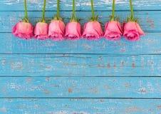 Romantische Liebe blüht, schöne rosa Rosen auf hellblauem hölzernem Hintergrund mit Kopienraum Lizenzfreie Stockbilder